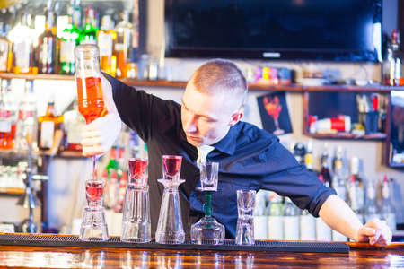 Young professional barman in action making cocktail drinks
