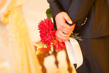 Beautiful wedding bouquet in hands of the bridegroom
