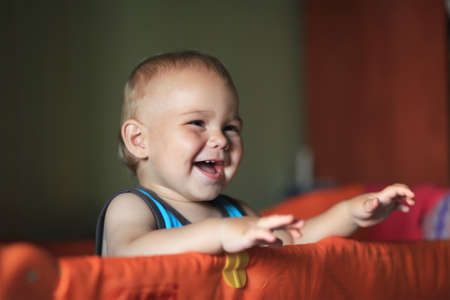 playpen: Portrait of a happy laughing baby standing in a cot