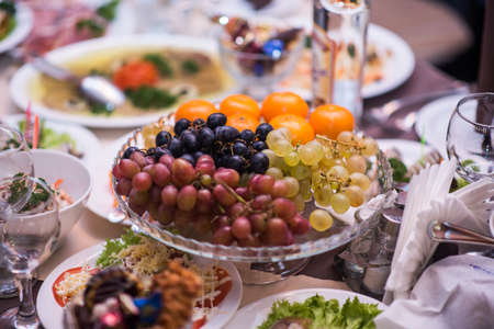 Fruits - Grapes, pears, tangerines. Against the background of the table with appetizers. Foto de archivo