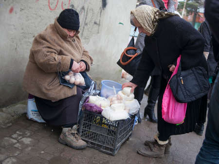 KUTAISI, GEORGIA - FEBRUARY 23, 2016: .Old woman farmer sells his cheese and eggs. Editorial