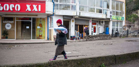 KUTAISI, GEORGIA - FEBRUARY 23, 2016: Woman carries goods walking on old street. Editorial
