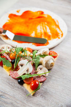 Dough basis covered with ketchup and ingredients for pizza. On a wooden table.