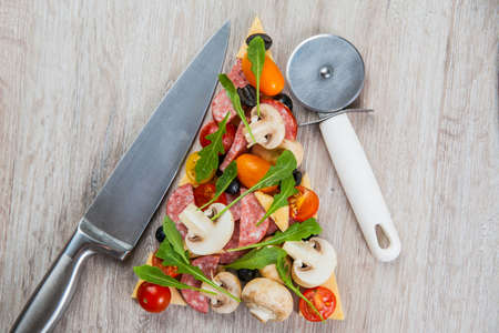 pizza cutter: Creative composition of ingredients tomatoes, cheese, salami, mushrooms, arugula, olives in the form of a slice of pizza with pizza cutter and knife, Stock Photo