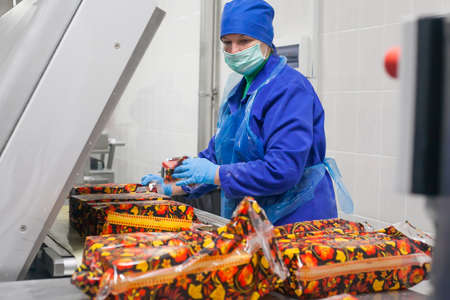 packer: SHUCHIN, BELARUS - JANUARY 26, 2015.The woman is engaged in the packaging of cheese on a cheese factory.