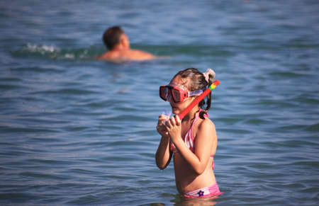 DIDIM, TURKEY - JULY 9 2014. Girl playing with toys on the sea.