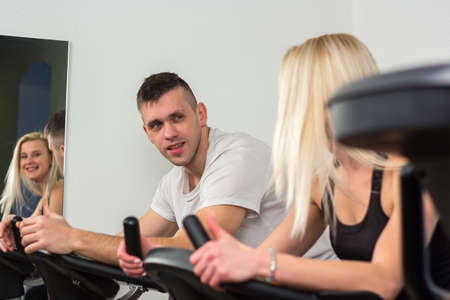 cardio workout: Young man and woman biking in the gym, exercising legs doing cardio workout cycling bikes.