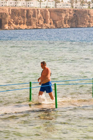 SHARM EL SHEIKH, EGYPT - JULY 9, 2019. a man walking in the sea on a background of hotels.