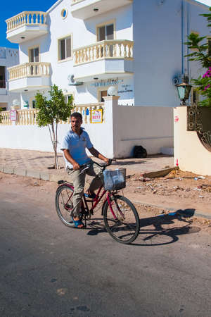 SHARM EL SHEIKH, EGYPT - JULY 9, 2009. cyclist passing by typical colourful house. Editorial