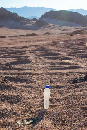 mpty crumpled plastic bottles of water abandoned on the desert.