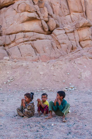 SHARM EL SHEIKH, EGYPT - JULY 9, 2009. Three children are sitting in the desert, and looking into the distance. Editorial
