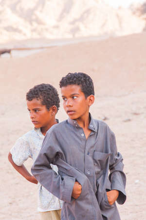 SHARM EL SHEIKH, EGYPT - JULY 9, 2009. Two sad child standing in the desert, and looking into the distance.