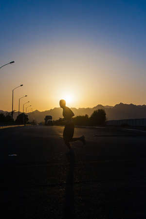 man running at sunset on a background of mountains.