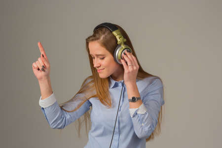 attractive girl with headphones on gray background.