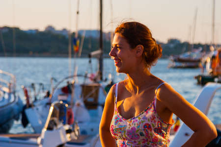 beautiful woman watching the sunset, standing on the background of yachts. Foto de archivo