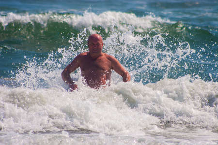 CONSTANTA, ROMANIA - AUGUST 21 2010. The happy man jumping in the sea Editorial