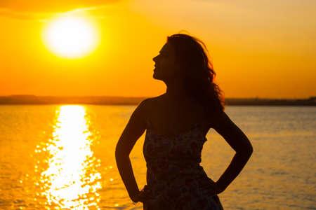 beautiful woman watching the sunset while sitting near the water.