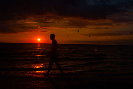 Silhouette of running man against the colorful sky. Silhouette of running man on sunset fiery background.