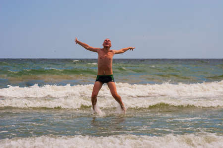 The happy young man jumping in the sea,