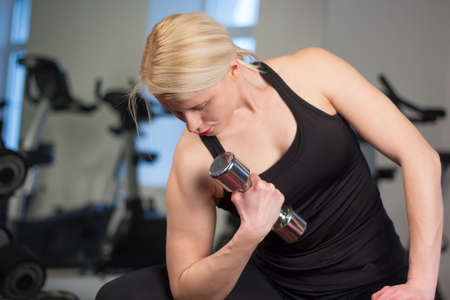 sexy young athletics girl doing dumbbells press exercises. Fitness muscled woman in black sport clothing workout on bench in gym. Foto de archivo