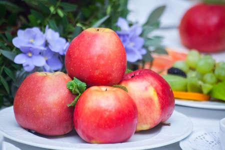 Manzanas rojas en un plato en la mesa blanca