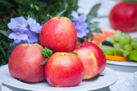 vitamin rich: Red apples in a plate on white table Stock Photo