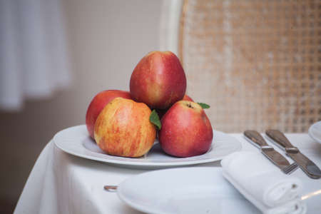 Red apples in a plate on white table Foto de archivo