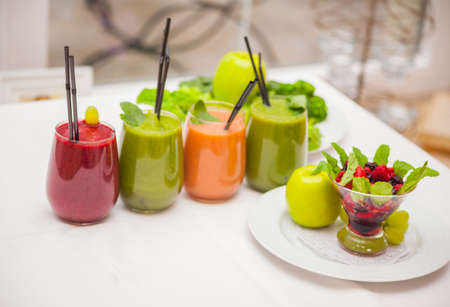 Red and green healthy smoothies with fresh ingredients on table Foto de archivo