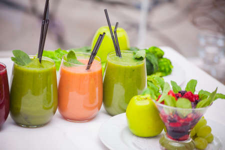 Red and green healthy smoothies with fresh ingredients on table Stock Photo