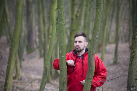 Trendy handsome man posing in spring park alone. Stock Photo