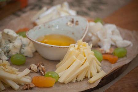 Surtido de queso con miel y uva en un fondo moderno pizarra de corte.