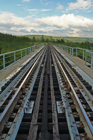 mainline: Outgoing in the far on the rails of a railway bridge Stock Photo