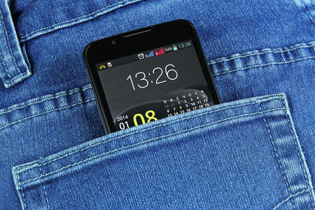 black phone in jeans pocket with the included screen closeup photo