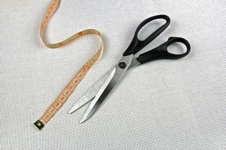 needlewoman: scissors and measuring tape on white fabric background closeup