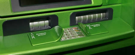 panel ATM mechanisms dispensing and receiving money closeup photo