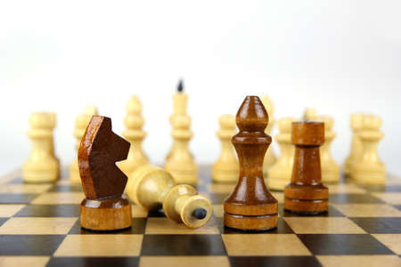 light and dark chess pieces on a chessboard on a light background photo