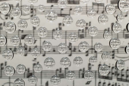 musical notation in drops of water on a background of blurred image of notes photo