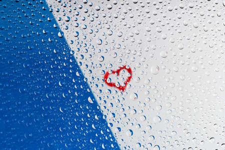 heart through water drops on glass on white and blue blurred background photo