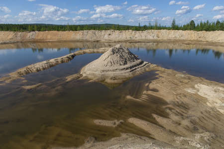 sand quarry: abandoned sand quarry with a mountain of sand and water in good weather Stock Photo