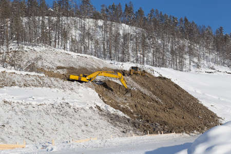 carry out: excavator and bulldozer carry out mining operations on a clear winter day
