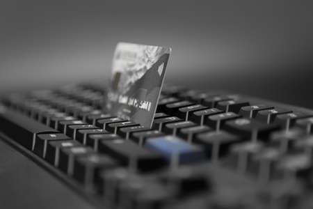bankcard: bankcard with a symbol of contactless technology on the background of a computer keyboard Stock Photo