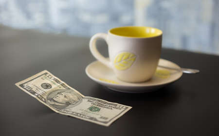 concept of a ten dollar tip on a dark table with a blurred background