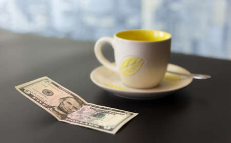 gratuity: concept of a five dollar tip on a dark table with a blurred background