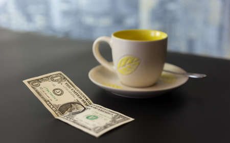 gratuity: concept of a dollar tip on a dark table with a blurred background