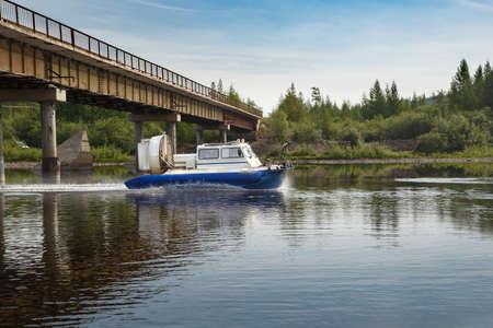 hovercraft: An air-cushion boat passes a bridge on a river