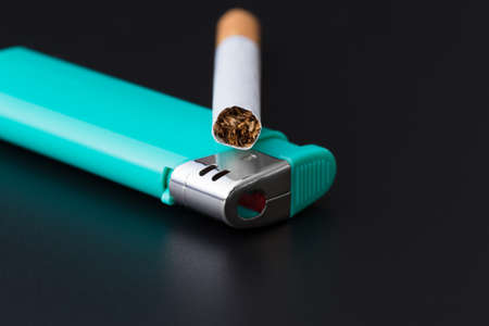 cigarette lying on a green lighter on a dark background closeup