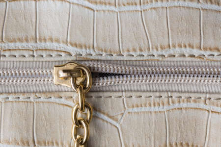 White plastic zipper sewn on to leather goods, close-up