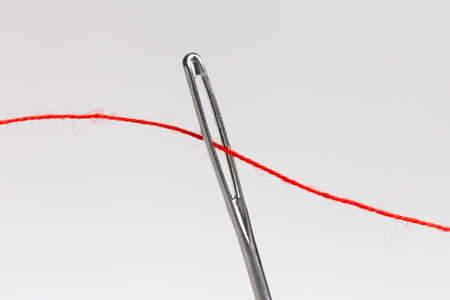 Red string threaded through the eye of a needle
