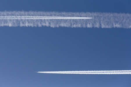 Two planes in clear sky leaving vapor trail on a collision course Фото со стока