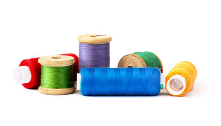 Multi-colored threads on wooden and plastic spools, on a white background.
